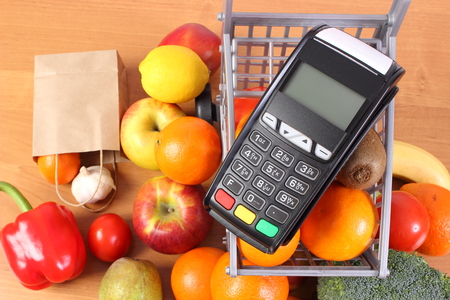 Payment terminal, credit card reader and fresh fruits and vegetables with plastic shopping carts, cashless paying for shopping, finance concept