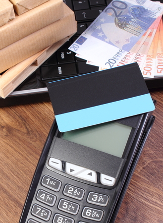 euro pallet: Payment terminal with contactless credit card, currencies euro, laptop and small wrapped boxes on wooden pallet, paying for products and shipping Stock Photo