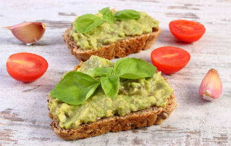 Ingredients and freshly prepared sandwiches with paste of avocado, rye bread, cherry tomatoes, garlic, basil, concept of healthy food, nutrition and omega fatty acids