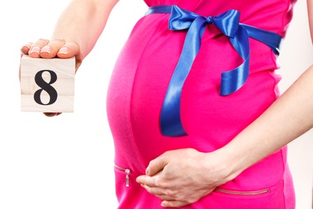 Pregnant woman in pink dress with blue ribbon showing number of eighth month of pregnancy, concept of extending family and expecting for newborn