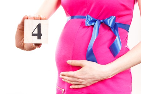 4 months belly: Pregnant woman in pink dress with blue ribbon showing number of fourth month of pregnancy, concept of extending family and expecting for newborn