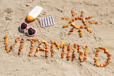 Medical pills, inscription vitamin D made of amber stones and accessories for sunbathing on sand at beach, concept of vacation time and prevention of vitamin D deficiency