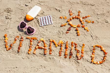 Pigułki medyczne, napis witamina D z bursztynu i akcesoria do opalania na piasku na plaży, pojęcie czasu na wakacje i zapobieganie niedoborowi witaminy D