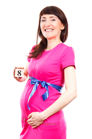 Happy smiling pregnant woman in pink dress with blue ribbon showing number of eighth month of pregnancy, concept of extending family and expecting for newborn