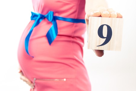 ninth: Vintage photo, Pregnant woman in pink dress with blue ribbon showing number of ninth month of pregnancy, concept of extending family and expecting for newborn Stock Photo