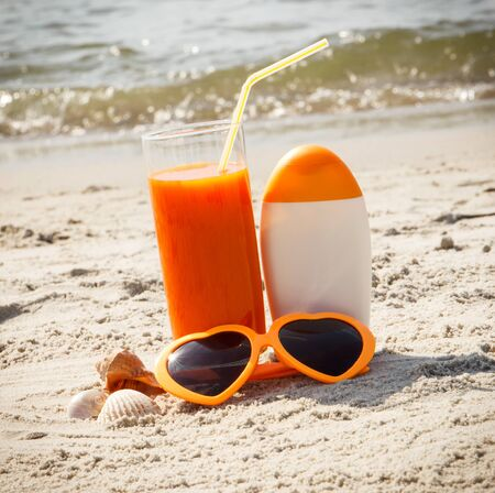 Carrot juice, sunglasses and sun lotion on sand at beach, concept of prevention of vitamin A deficiency, beautiful and lasting tan Stock Photo