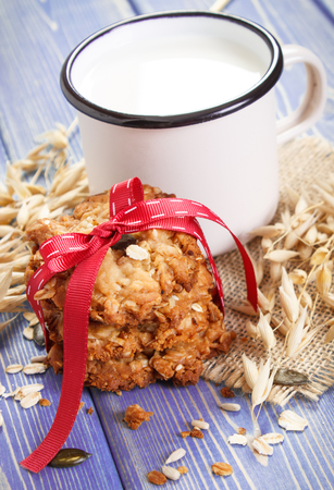 Fresh baked homemade crusty oatmeal cookies, ingredients for baking and ears of oat, concept of delicious healthy dessert