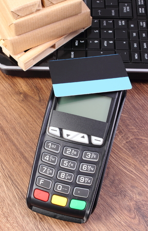 contactless: Payment terminal with contactless credit card, laptop and small wrapped boxes on wooden pallet, cashless paying for products and shipping