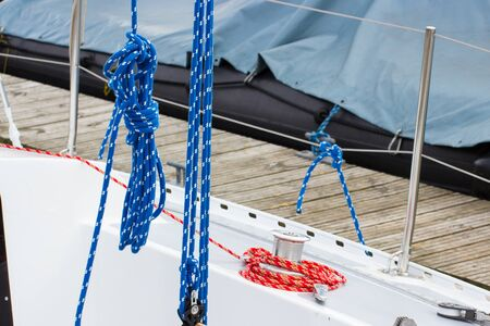 Yachting, colorful coiled rope and bollard on deck of sailboat, details and part of yacht