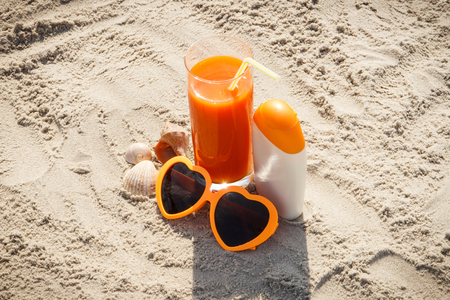 deficiency: Carrot juice, sunglasses and sun lotion on sand at beach, concept of prevention of vitamin A deficiency, beautiful and lasting tan Stock Photo