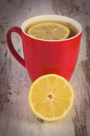 warming therapy: Vintage photo, Fresh lemon and cup of hot tea with lemon on old rustic board, healthy nutrition, strengthening immunity and alternative therapy
