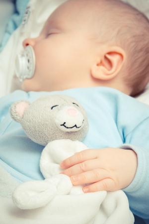 Foto de época, dulce bebé recién nacido con chupete durmiendo con oso de peluche de juguete