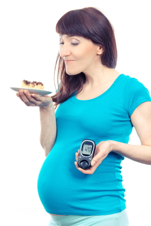 Pregnant woman holding glucometer with result of measurement sugar level and piece of cheesecake, concept of diabetes during pregnancy, expecting for newborn Stock Photo