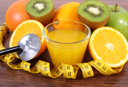 measuring cup: Medical stethoscope and tape measure with fresh ripe fruits and glass of juice on wooden plank, grapefruit orange kiwi apple, healthy lifestyles nutrition and strengthening immunity Stock Photo