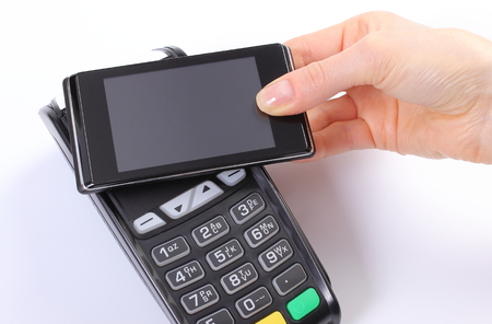 paying: Banking and finance concept, Hand of woman using payment terminal with mobile phone with NFC technology, credit card reader