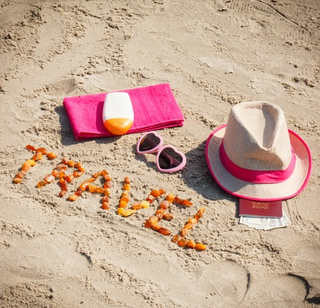 Inscription travel made of amber stones, accessories for sunbathing and passport with currencies dollar on sand at beach, concept of sunbathing, travel and vacation time Stock Photo