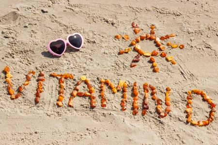선글라스, 비문 비타민 D 및 모양의 모래 해변, 휴일의 개념 및 비타민 D 결핍증의 개념에 호박 돌으로 만든 태양의 모양