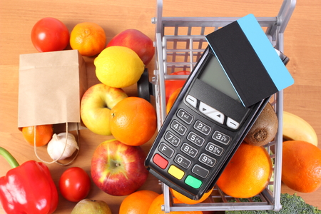 Payment terminal, credit card reader with contactless credit card, fresh fruits and vegetables with plastic carts, cashless paying for shopping concept Stock Photo