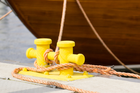 Rope and yellow mooring bollard in port, closeup and detail of seaport and yachting Stock Photo