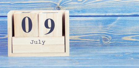 Vintage photo, July 9th. Date of 9 July on wooden cube calendar, copy space for text on board
