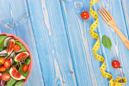 Fruit and vegetable salad in bowl and fork with tape measure, concept of diet, slimming, healthy lifestyles and nutrition, copy space for text or inscription on boards