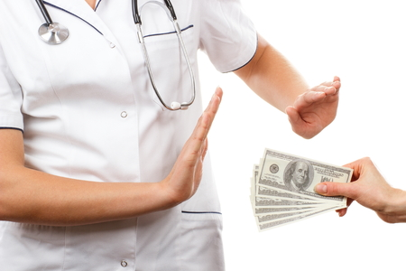 Woman doctor with stethoscope refusing bribes or kickbacks, currencies dollar, patient giving money for medical services, concept of corruption