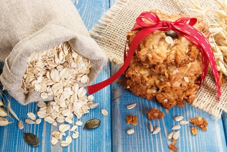 Fresh baked crusty oatmeal cookies, flakes in jute bag and ears of oat, concept of delicious healthy dessert Stock Photo