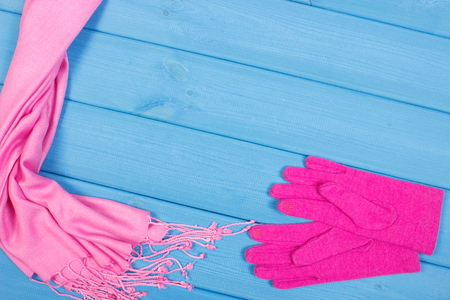 Woolen gloves and pink shawl for woman on blue boards, warm clothing for autumn or winter, womanly accessories Stock Photo