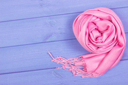 Woolen pink shawl for woman, warm clothing for autumn or winter, womanly accessories, copy space for text on boards Stock Photo