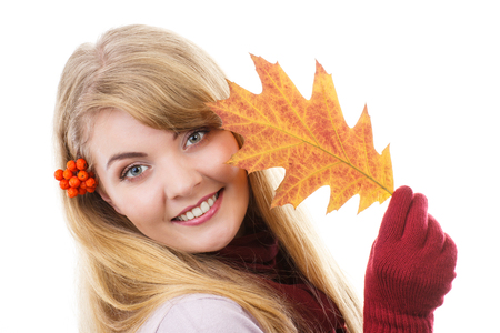 Happy smiling girl with rowan in hair wearing woolen shawl, gloves and holding autumnal leaf