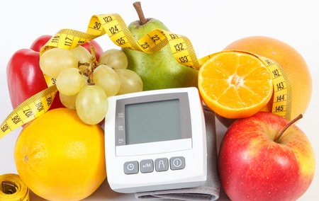 Blood pressure monitor, fresh fruits with vegetables and tape measure, healthy lifestyle, slimming and prevention of hypertension concept
