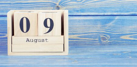 Vintage photo, August 9th. Date of 9 August on wooden cube calendar, copy space for text on board