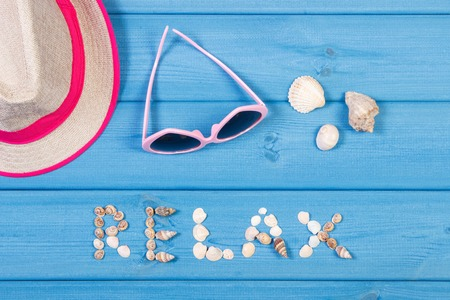 Inscription relax made of seashells, straw hat and sunglasses on boards, summer and vacation time conept Stock Photo