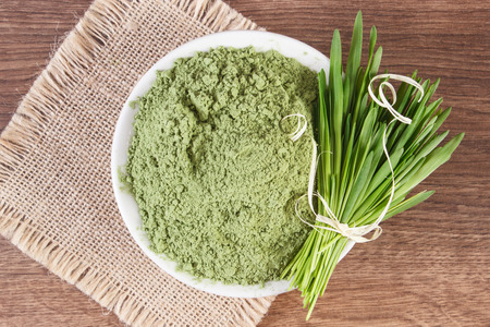 Barley grass with heap of young powder barley in bowl on jute canvas, healthy nutrition and lifestyle, body detox