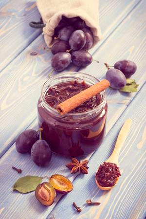 Vintage photo, Fresh plum jam or marmalade in glass jar, ripe fruits and spices on boards, concept of healthy sweet dessert