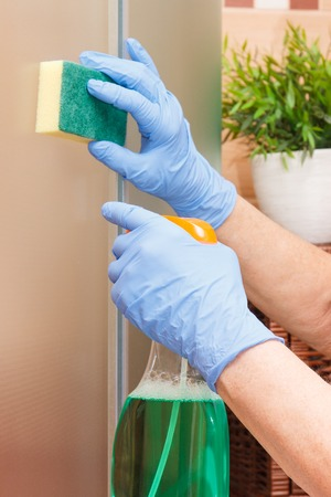 Hand of senior woman in protective gloves cleaning glass shower using sponge and detergent, concept of household duties