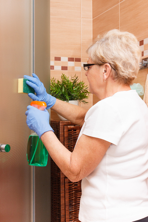 cabine de douche: Senior woman in protective gloves cleaning glass shower door using sponge and detergent, concept of household duties