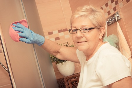 microfiber: Elderly senior woman in protective rubber gloves using pink microfiber cloth and cleaning shower glass in bathroom, concept of household duties