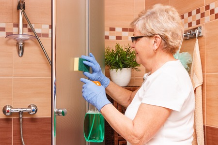 Elderly senior woman in protective gloves wiping glass shower cabin using sponge and detergent, concept of house cleaning and household duties