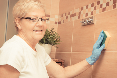 Elderly senior woman in protective rubber gloves wiping bathroom tiles using sponge, concept of house cleaning and household duties