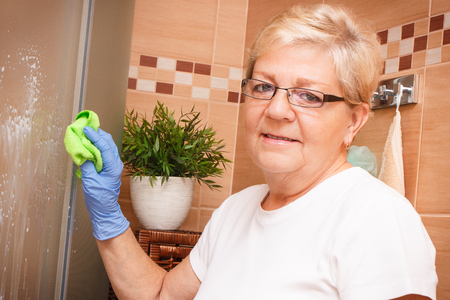 cabine de douche: Elderly senior woman in protective rubber gloves using microfiber cloth for cleaning shower glass in bathroom, concept of household duties