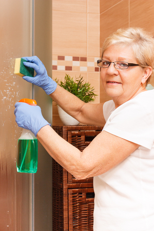 Senior woman in protective rubber gloves using sponge for cleaning shower in bathroom, concept of household duties Zdjęcie Seryjne