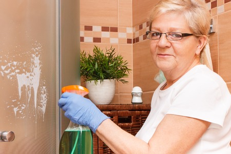 Elderly senior woman in protective rubber gloves using detergent for washing and wiping shower in bathroom, concept of house cleaning