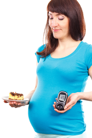 Unhappy pregnant woman holding glucometer with result of measurement sugar level and piece of cheesecake, concept of diabetes during pregnancy