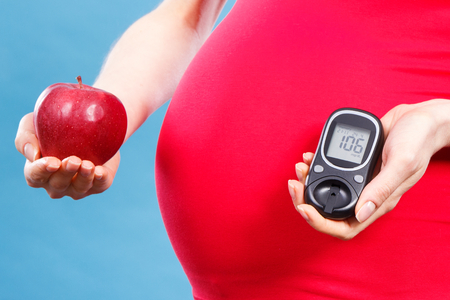 Pregnant woman holding fresh apple and glucose meter with good result of measurement sugar level, concept of nutrition, diabetes during pregnancy 版權商用圖片
