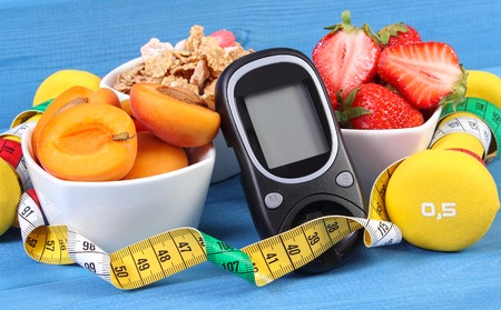 Glucose meter for measuring sugar level, healthy food, dumbbells for fitness and tape measure, concept of diabetes, slimming and healthy lifestyle