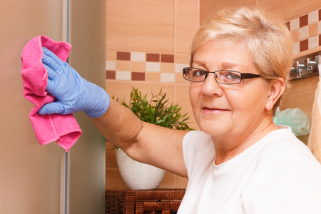 bath: Elderly senior woman in protective rubber gloves wiping shower cabin using pink microfiber cloth, concept of house cleaning and household duties