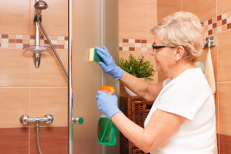Elderly senior woman in protective gloves cleaning shower using sponge and detergent, concept of household duties
