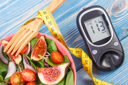 Fruit and vegetable salad, glucose meter with result of measurement sugar level and tape measure, concept of diabetes, diet, slimming, healthy lifestyles and nutrition Фото со стока