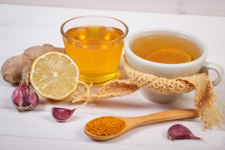 Cup of tea with lemon and ingredients for preparation warming beverage for flu and cold, health care concept